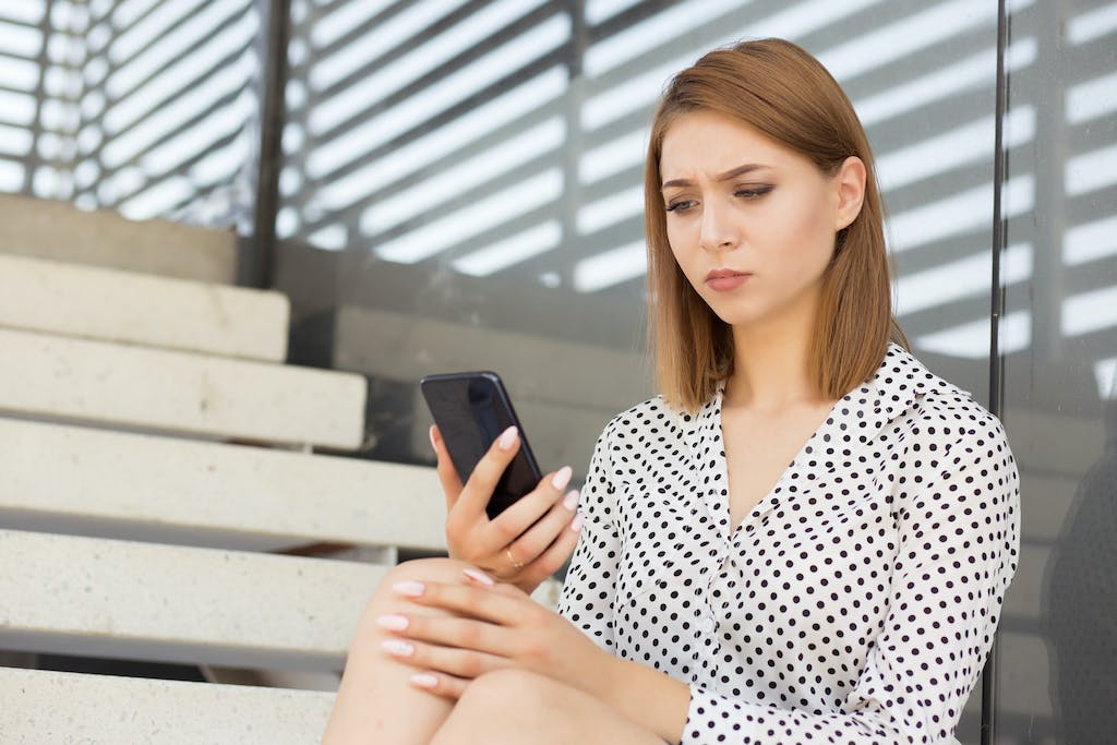 Woman looking at latest bill on phone