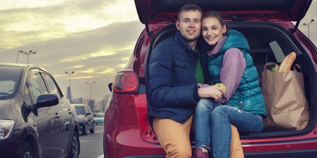 couple-sat-in-boot-of-car
