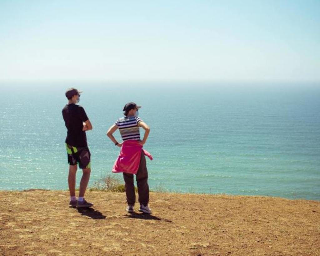 Man and woman looking around an empty beach wearing a facemask