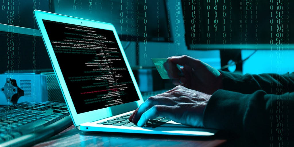 Cyber criminal with credit card hacking system at table, digital binary code on background