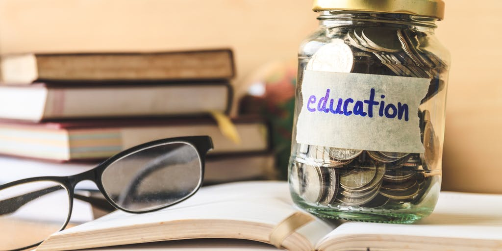 glasses on top of book next to jar with coins in stating education