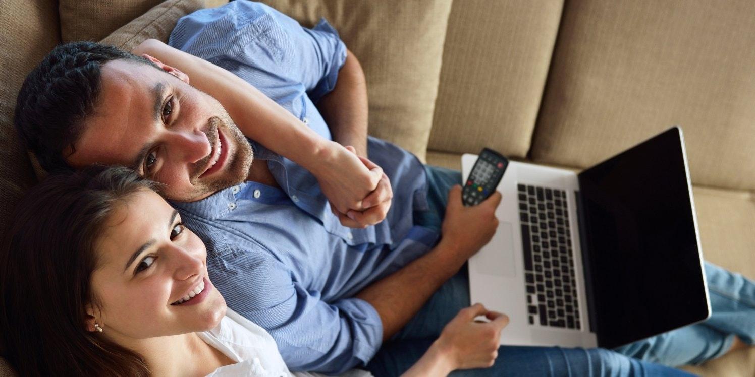 Happy couple on sofa using laptop