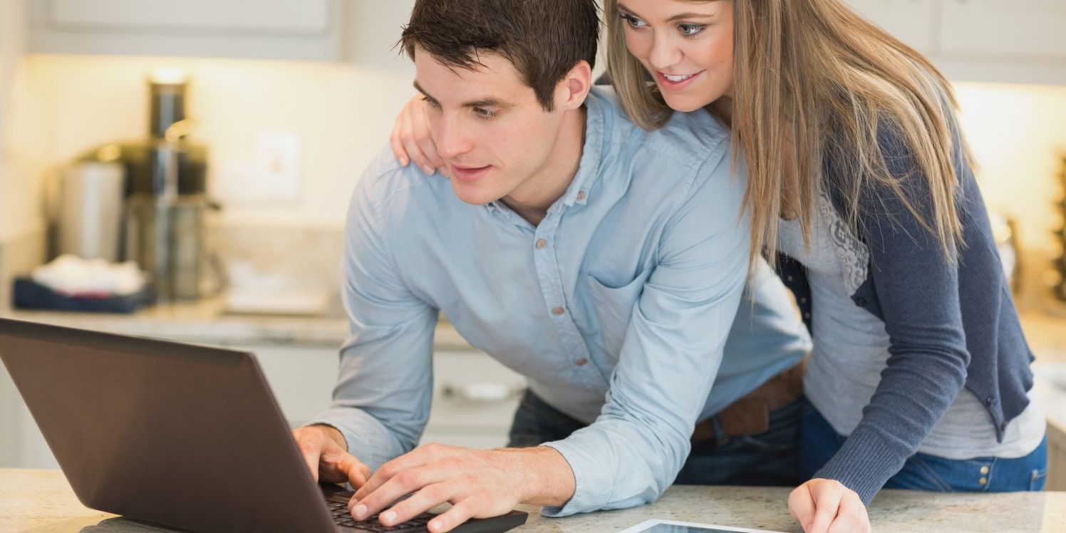 young-couple-using-laptop-in-kitchen