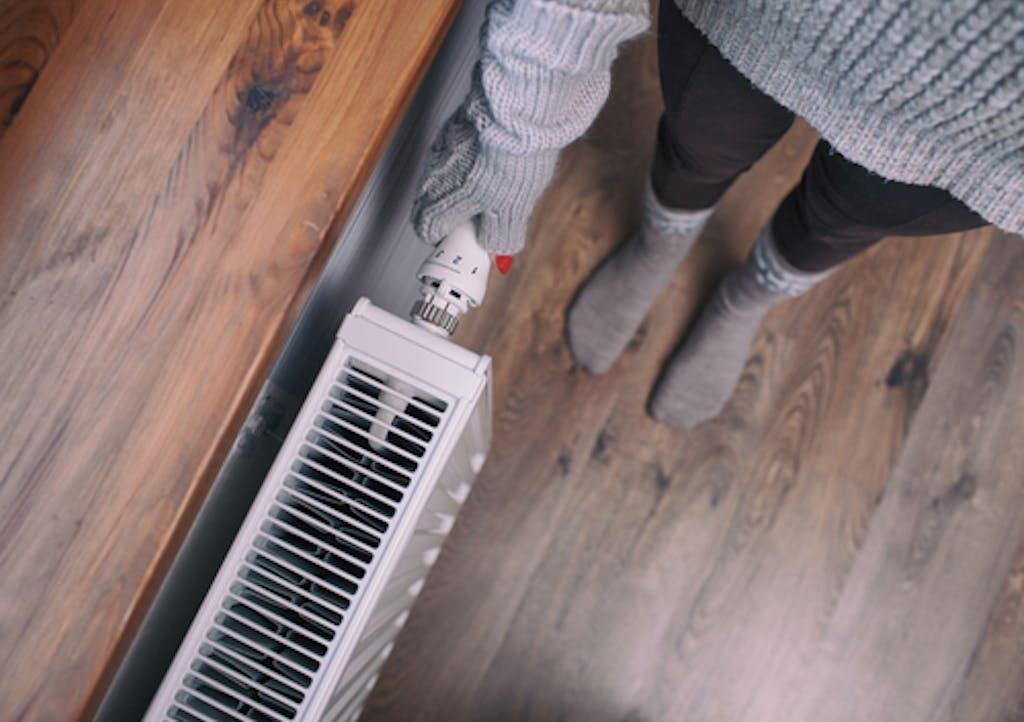 Woman in gloves feeling radiator
