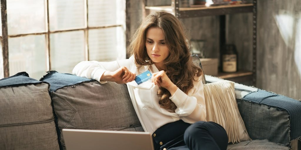 Woman holding a credit card while using a laptop
