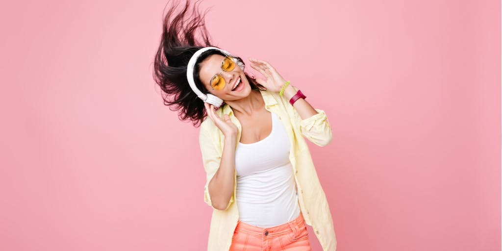 girl listening to music in front of pink background