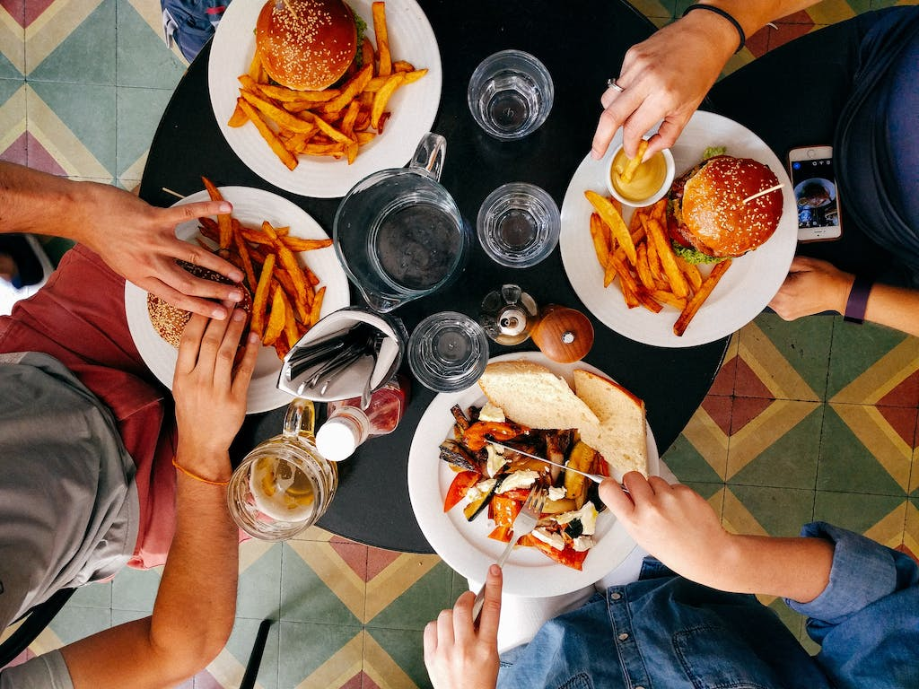 A birdseye view of a dining table with 4 people eating burgers.