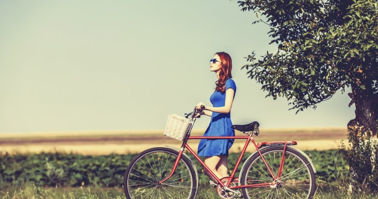 Young woman walking bicycle down countryside road in the sun