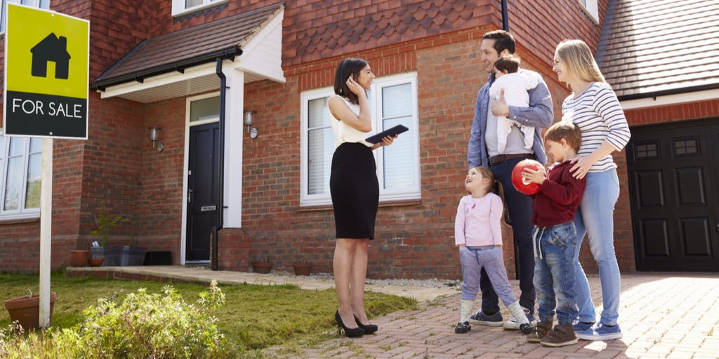 Estate agent outside house for sale speaking to family