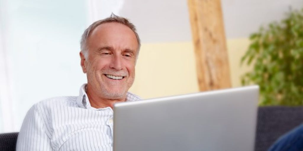 older man on sofa with laptop