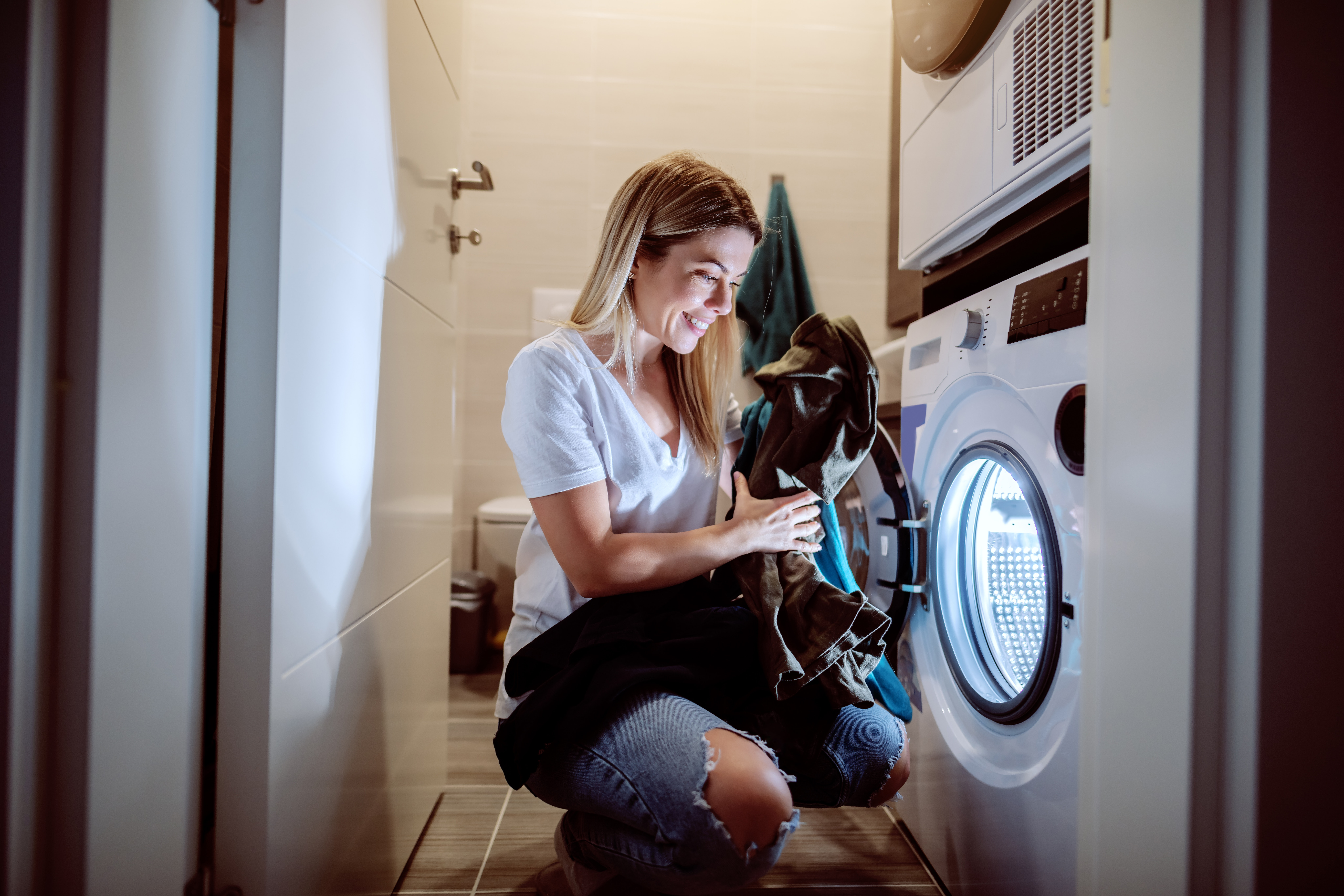 Woman using washing machine during Economy 7 hours