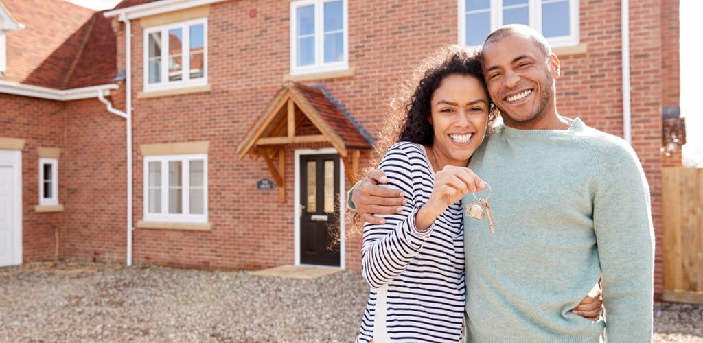 Image of man and woman holding keys to new home