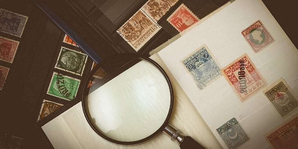 Photo of stamp collector's collection and magnifying glass