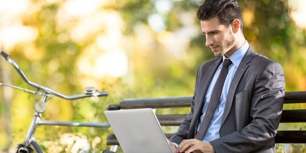 Businessman in a park sitting on a bench on his laptop