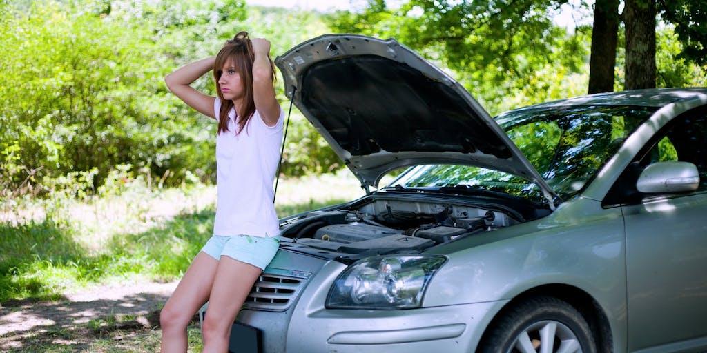 Girl standing by broken down car