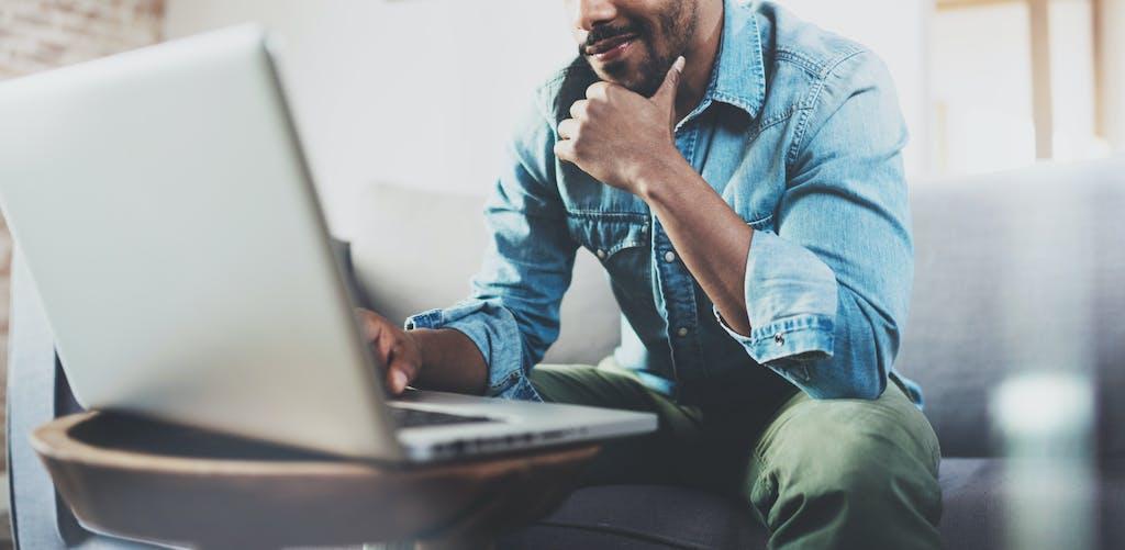 Man using postcode broadband checker on laptop