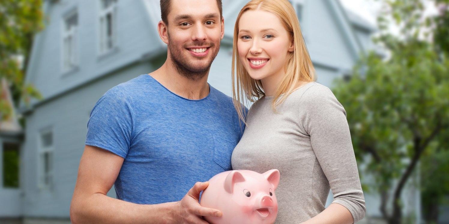 Couple holding piggy bank outside house