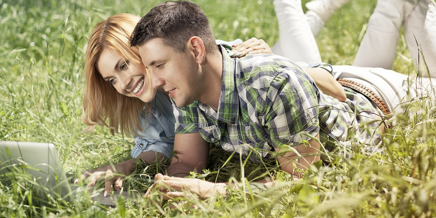 Young couple outside in garden using laptop