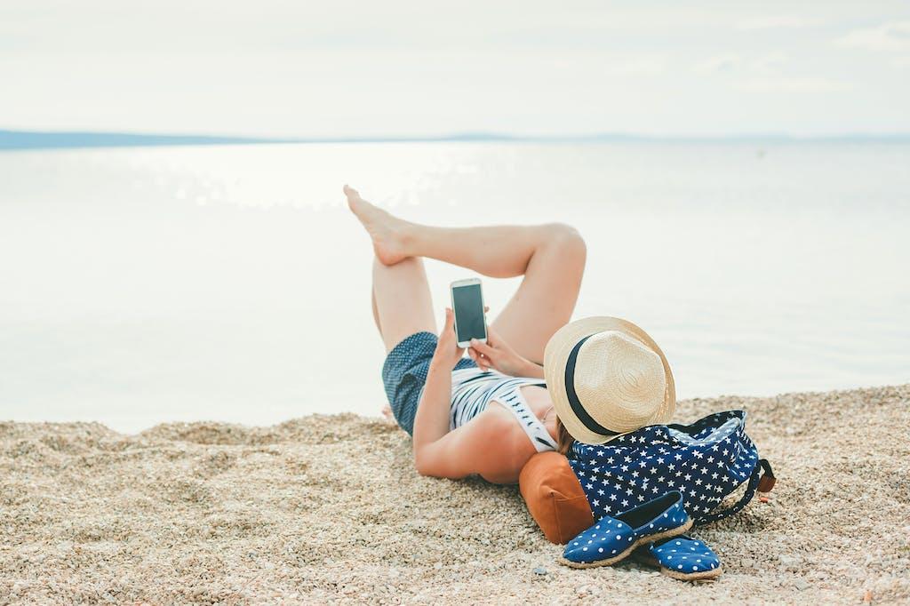 Woman using phone on beach holiday