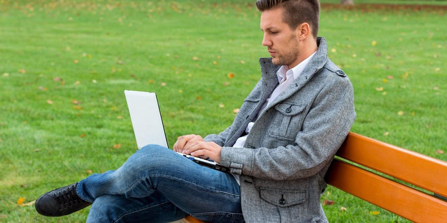 Man on park bench using laptop