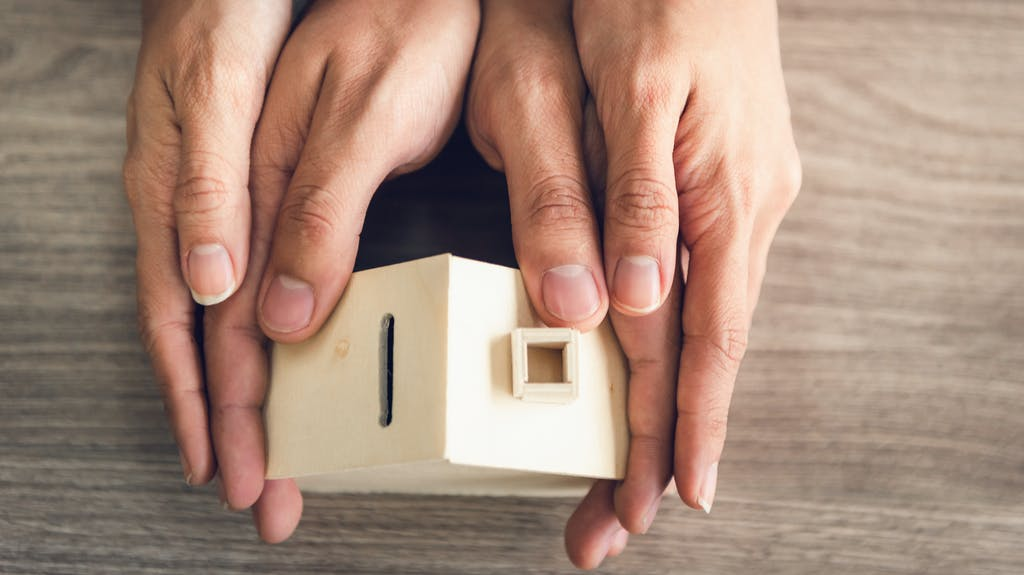 Couple Hands Holding Housing Model