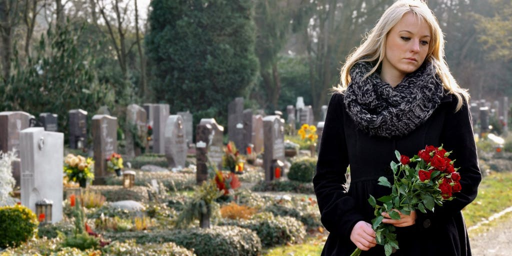 woman-holding-flowers-in-graveyard