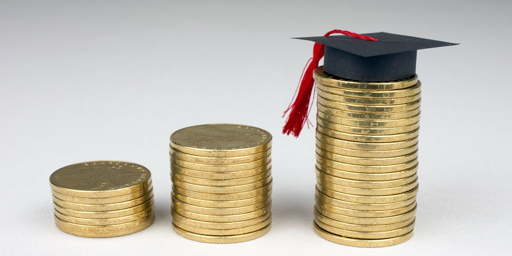 Picture of coins stacked up next to each other with a graduation cap on top of third stack of coins