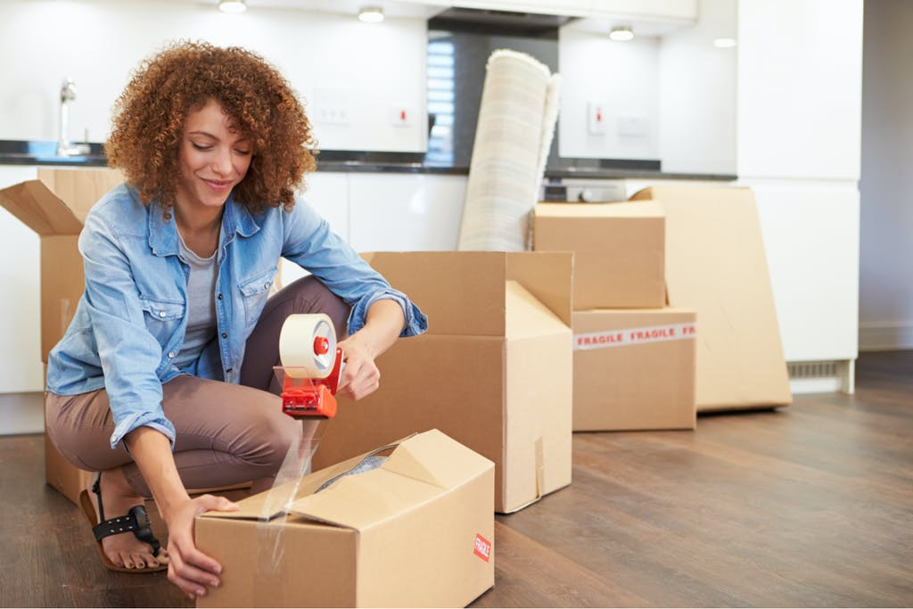 Woman taping boxes during moving house