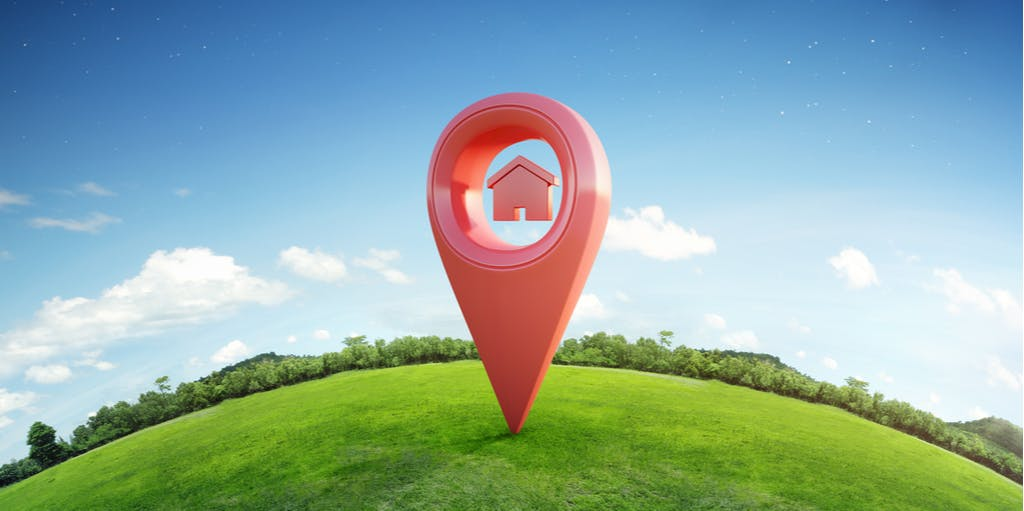 House symbol with location pin icon on earth and green grass in real estate sale.