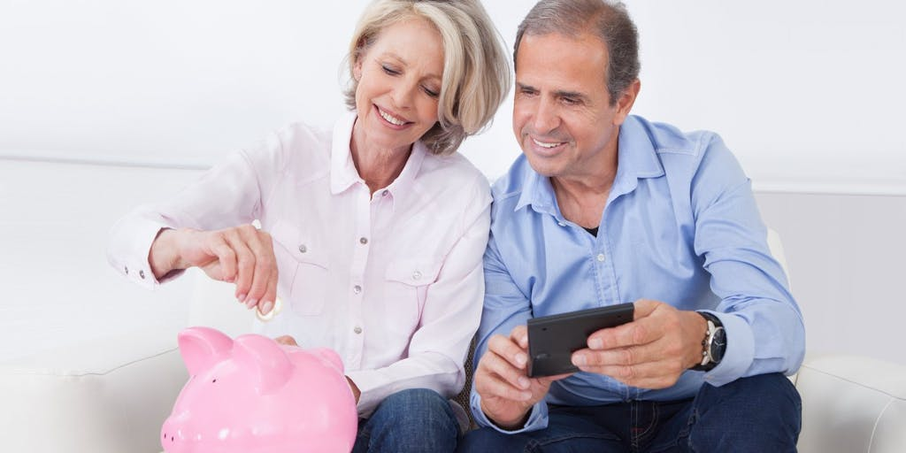 Older couple putting coins in piggy bank