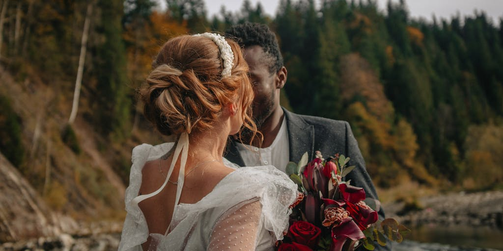An interracial couple of newlyweds walks along the shore of a mountain river.