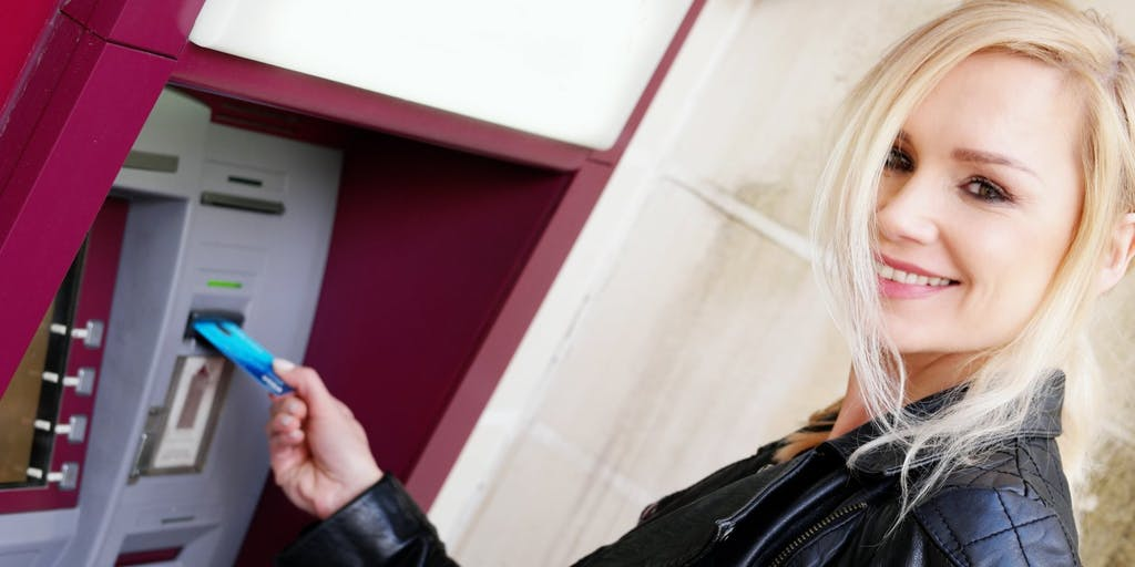 woman using cash machine with card
