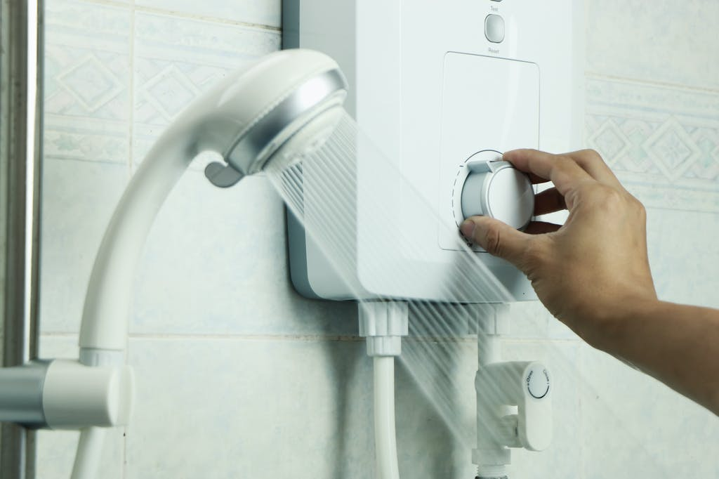 Person regulating hot water temperature in shower