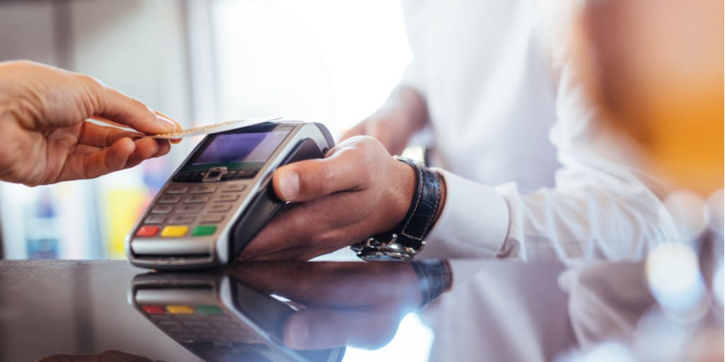 Photographic of a man making a transaction through contactless payment