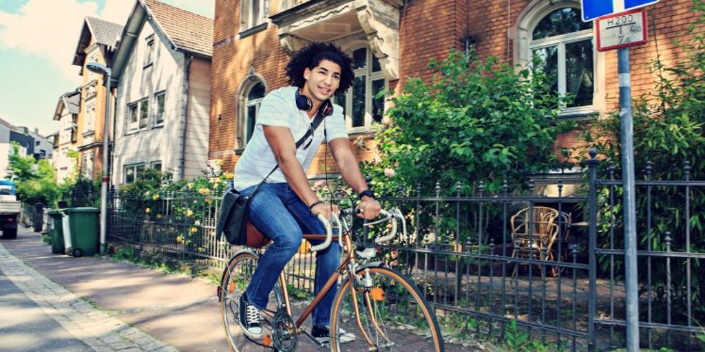 student-cycling-along-path