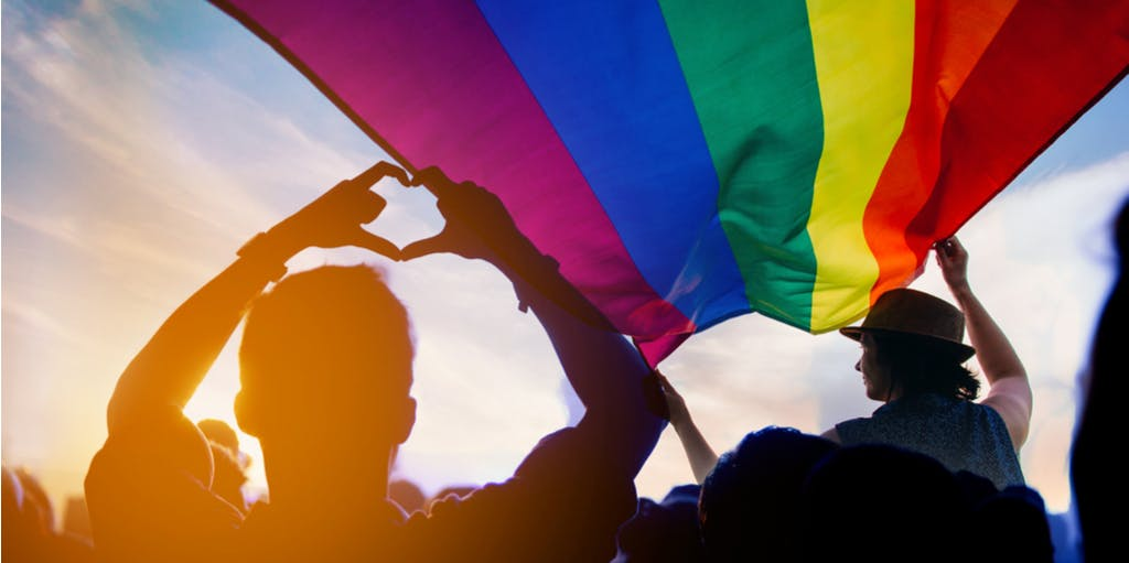 A picture of an LGBTQ+ flag with a crowd of people.