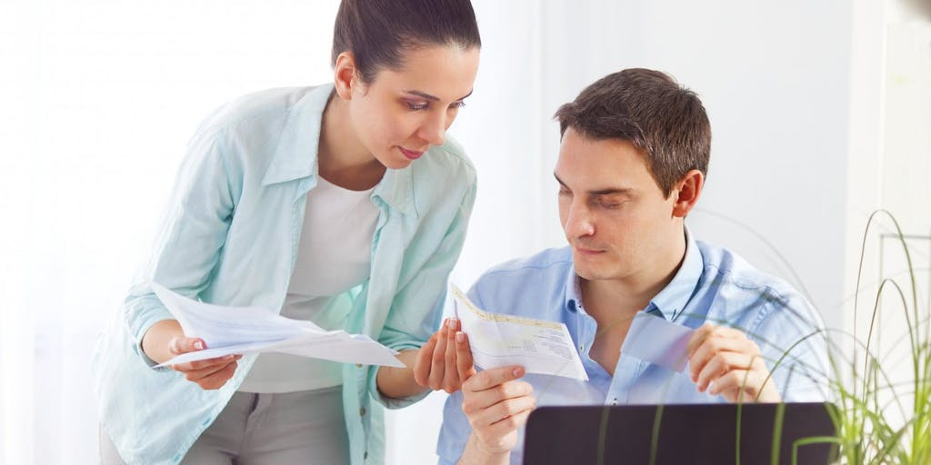 Couple comparing paperwork