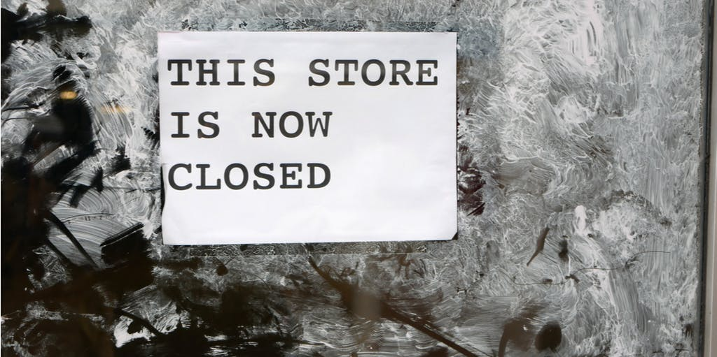 'this store is now closed' sign on door sprayed with white paint illustrating economic down turn on British high street