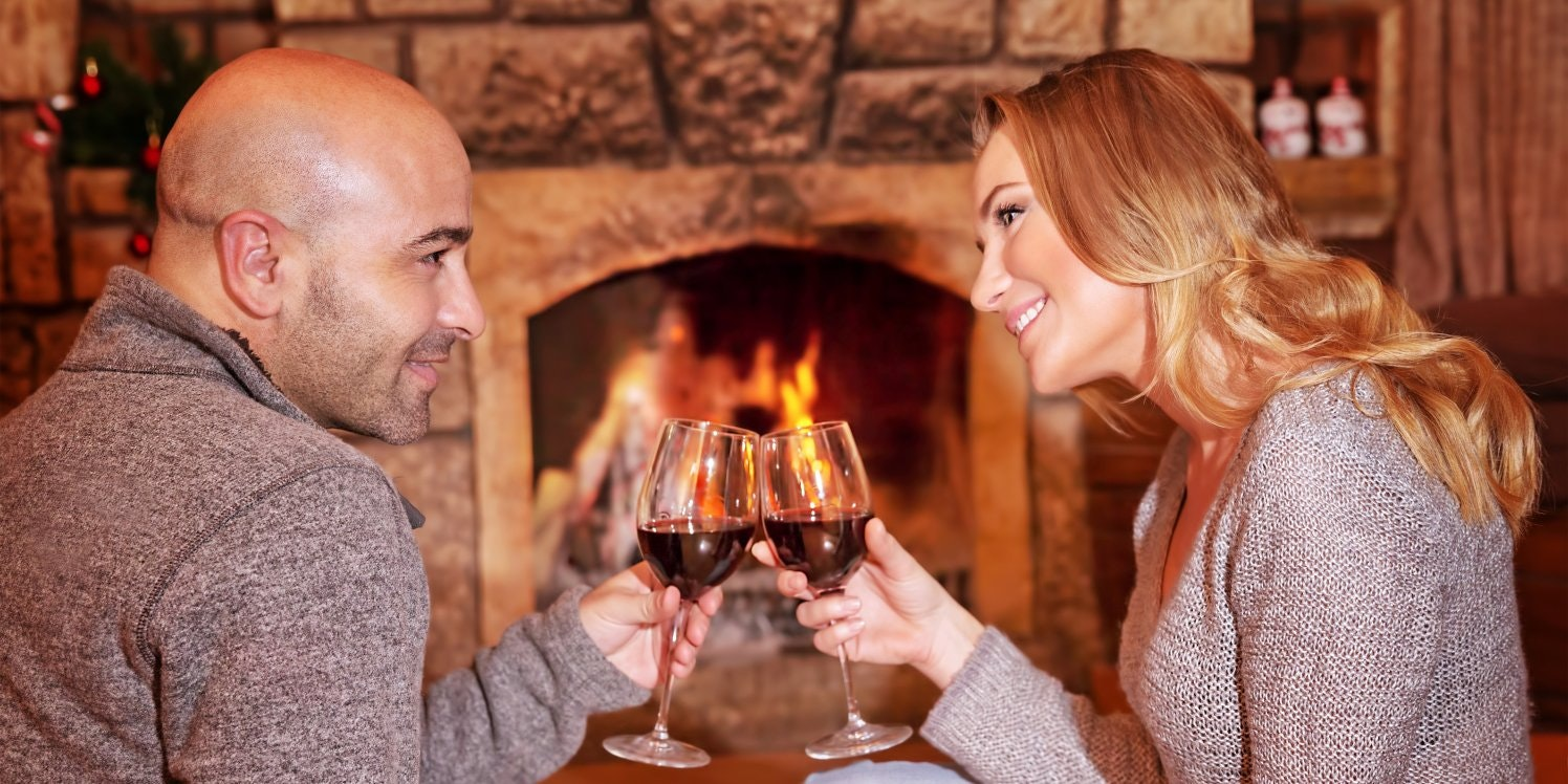 Couple clinking champagne glasses sitting by fireplace