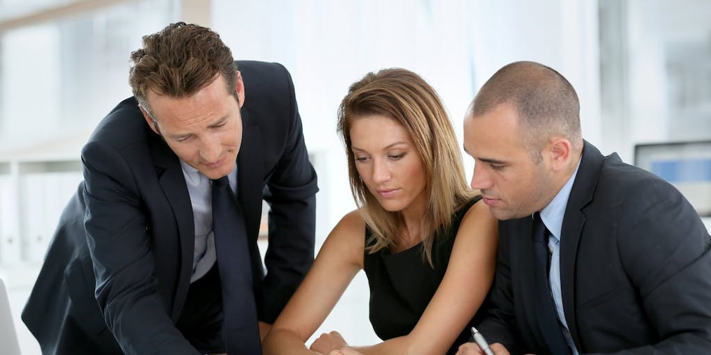 couple discussing paperwork with financial advisor