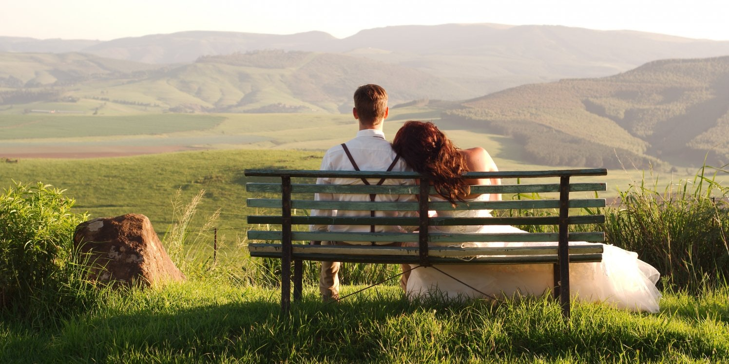 Newlywed couple sitting on park bench