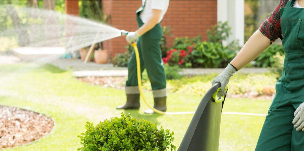 Image of two people gardening in green overalls, one person spraying house, the other person holding a chair