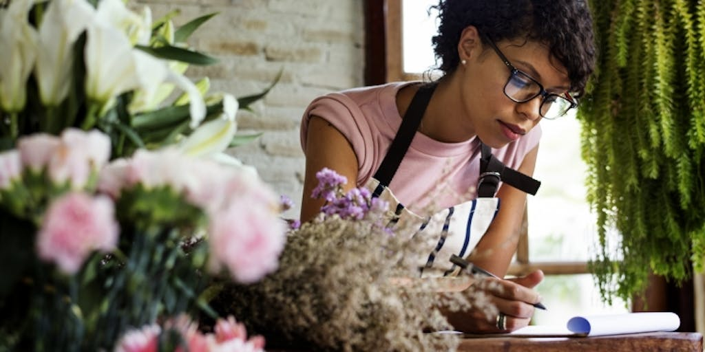 Woman in florist writing notes.