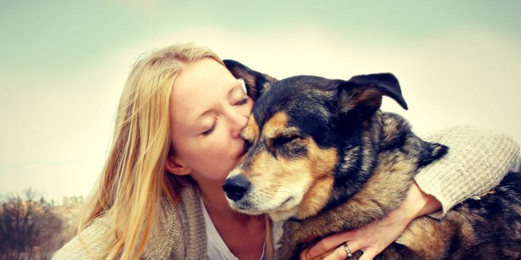 Woman kissing a dog on the head outside.