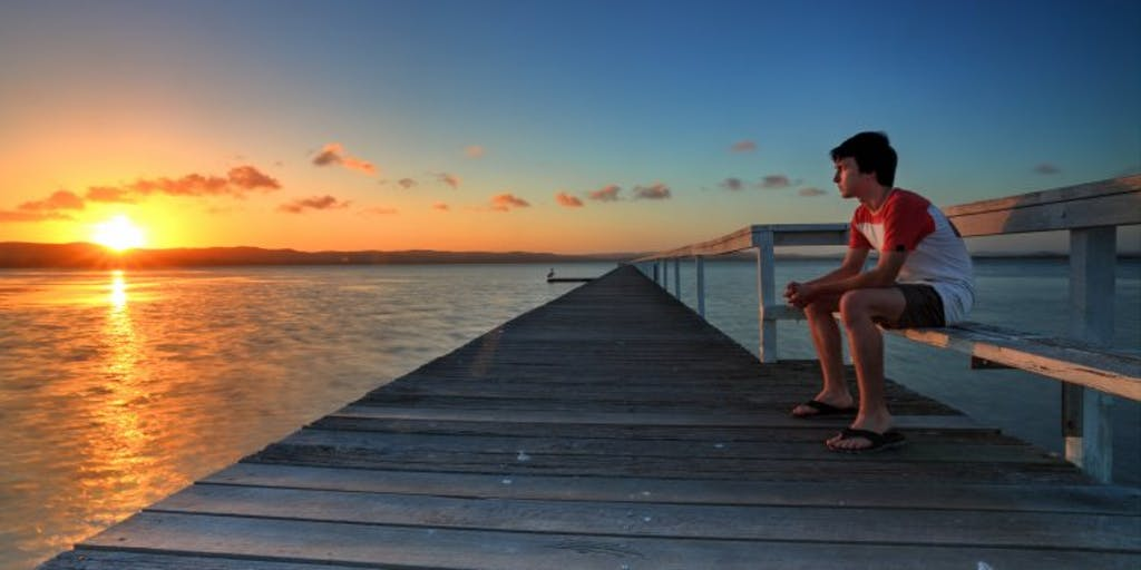 boy-watching-the-sunset-from-pier