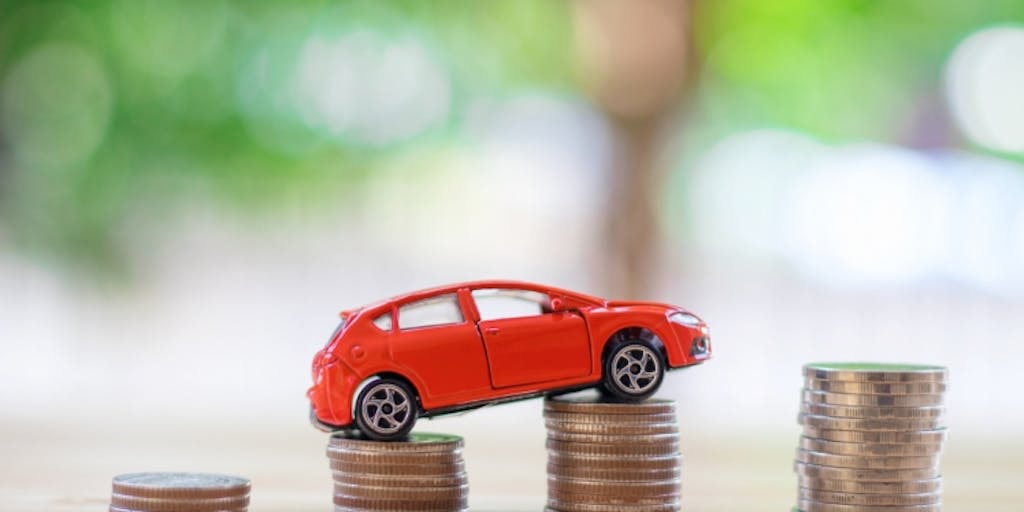 Toy car driving over coins