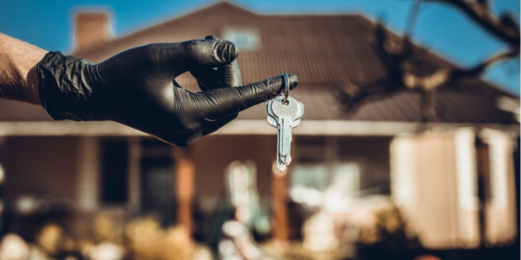 Photograph of a gloved hand holding keys in front of a house