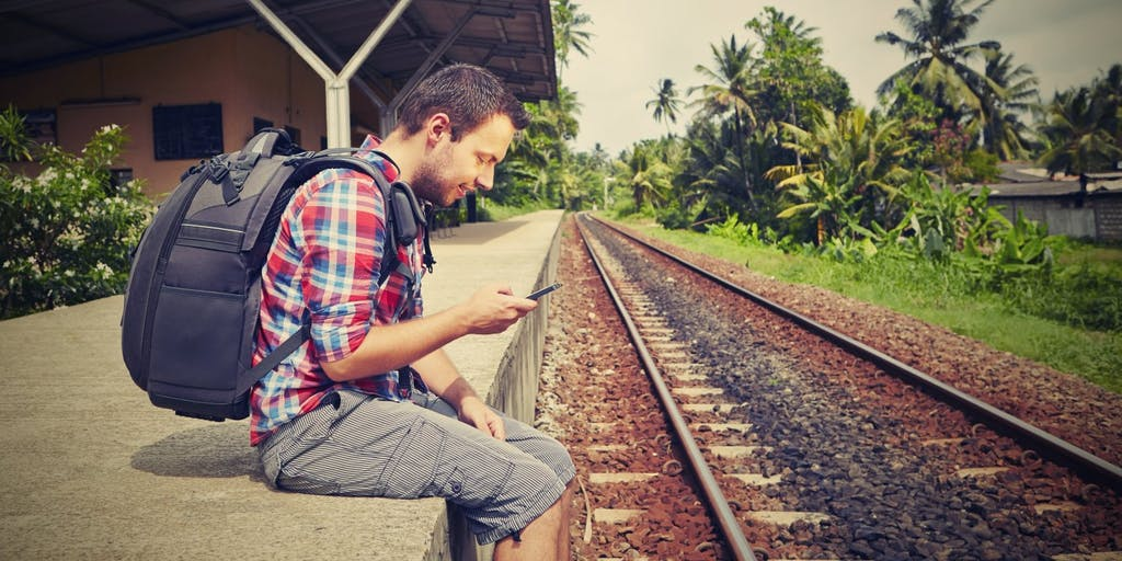 Young travel with backpack sitting by train tracks