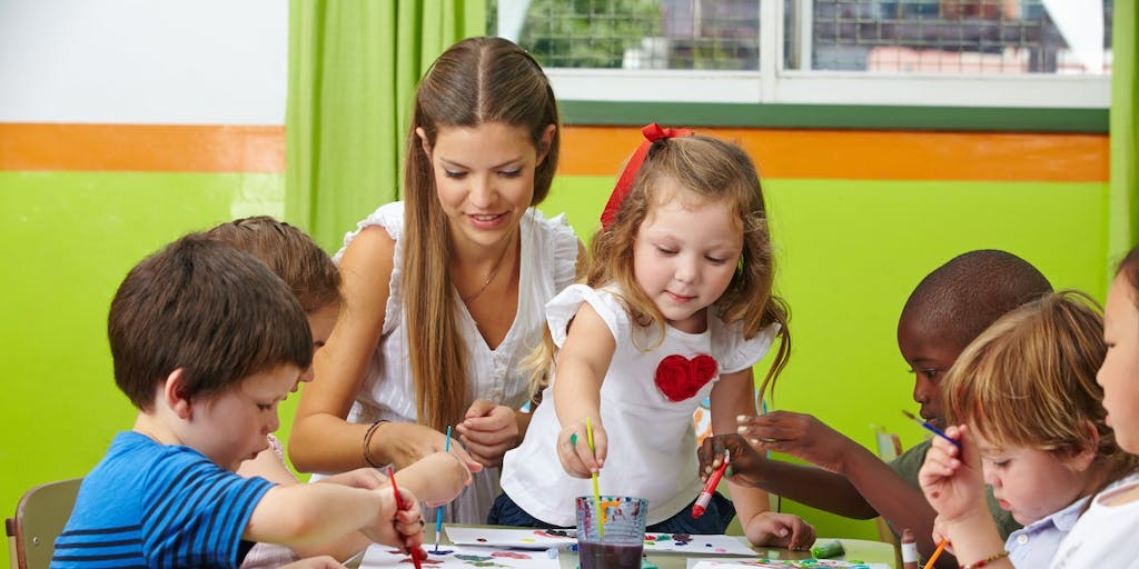 Teacher painting with kids at table