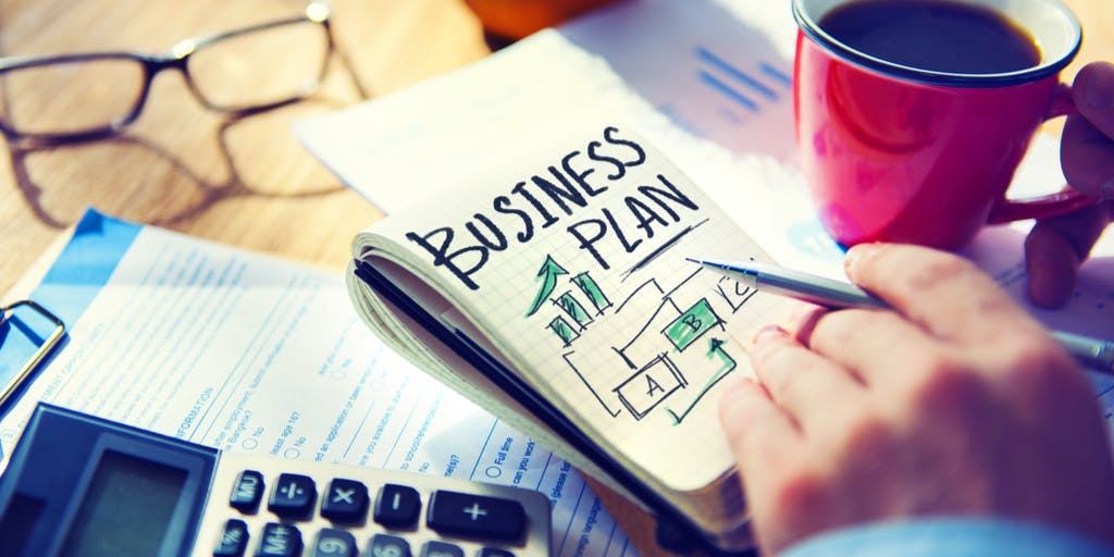 Image of business plan and someone writing one with a cup of coffee